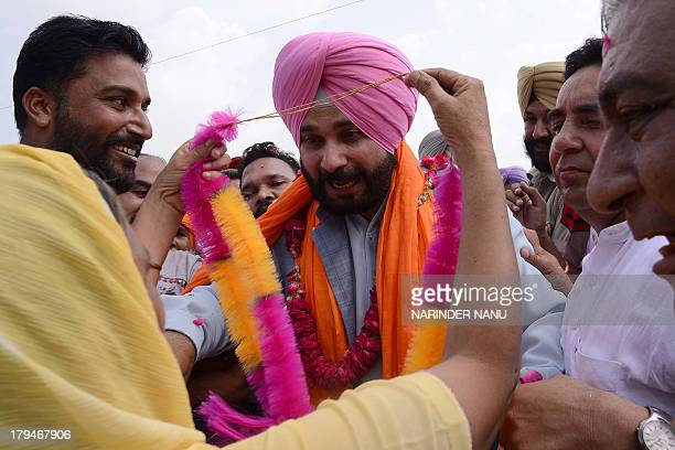 Members of the Bharatiya Janata Party garland former Indian cricketer and member of parliament Navjot Singh Sidhu on his return after remaining...