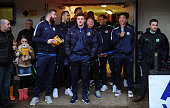 Members of the Blackburn team look on from undercover as heavy rain postpones the match during The Emirates FA Cup Third Round match between Newport...