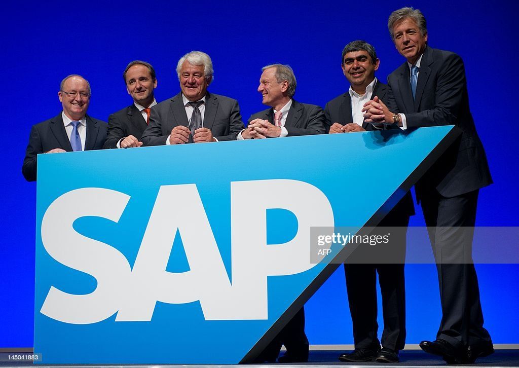 Members of the board of German business software giant SAP (L-R) Gerhard Oswald, co-chairman Jim Hagemann Snabe, supervisory board chairman Hasso Plattner, Werner Brandt, Vishal Sikka and co-chairman Bill McDermott pose in front of their company's logo during the annual general meeting of SAP on May 23, 2012 in Mannheim, western Germany. SAP said on May 22, 2012 it was acquiring US cloud-based e-commerce firm Ariba for $4.3 billion in a move boosting its arsenal against arch-rival Oracle. AFP PHOTO / UWE ANSPACH GERMANY OUT