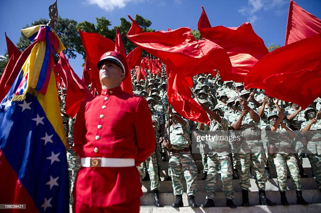 Members of the Bolivarian militias take part in a military parade during a meeting in Caracas on January 10, 2013. With Chavez ailing and absent, Venezuela's leftist government launches a new presidential term with a display of popular support on the day he was to be inaugurated. The Supreme Court cleared the cancer-stricken president to indefinitely postpone his re-inauguration and said his existing administration could remain in office until he is well enough to take the oath. AFP PHOTO/Raul ARBOLEDA