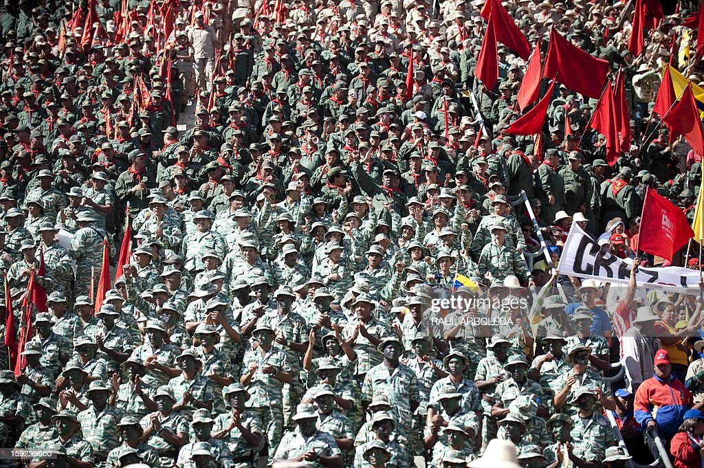 Members of the Bolivarian militias take part in a military parade during an event in homage of President Hugo Chavez, in Caracas on January 10, 2013. With Chavez ailing and absent, Venezuela's leftist government launches a new presidential term with a display of popular support on the day he was to be inaugurated. The Supreme Court cleared the cancer-stricken president,kwho is recovering from a fourth round of cancer surgery in Havana, to indefinitely postpone his re-inauguration and said his existing administration could remain in office until he is well enough to take the oath. The government has said that he is recovering from complications from surgery, most recently a severe pulmonary infection that had resulted in a 'respiratory insufficiency.' AFP PHOTO/Raul ARBOLEDA