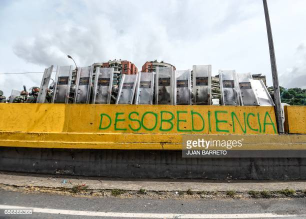 Members of the Bolivarian National Guard remain behind their shields next to a graffiti reading 'Disobedience' during a health care personnel march...