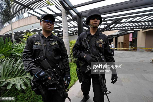 Members of the Bomb Squad secure the area following a shootout with thieves at the Greenbelt 5 shopping mall in Manila's financial district on...