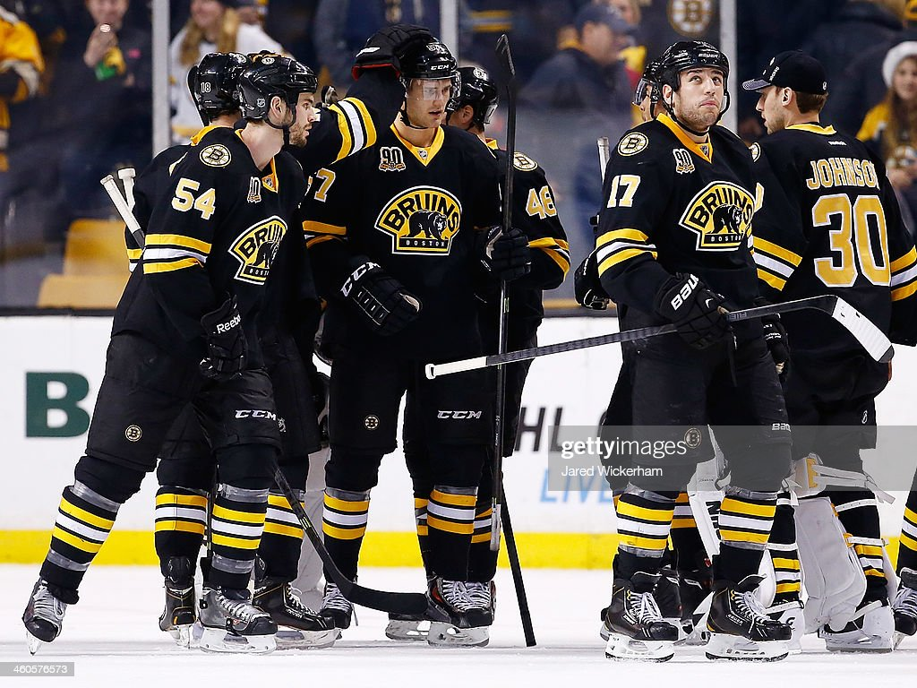 Members of the Boston Bruins congratulate teammate Justin Florek #57 following his first NHL game against the Winnipeg Jets during the game at TD Garden on January 4, 2014 in Boston, Massachusetts.