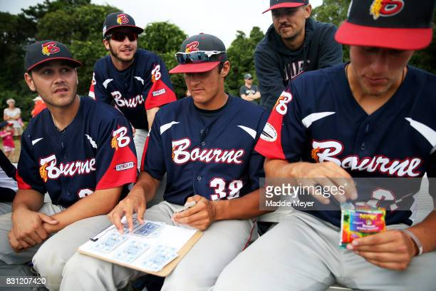 Members of the Bounre Braves play the card game President during game one of the Cape Cod League Championship Series against the Brewster Whitecaps...