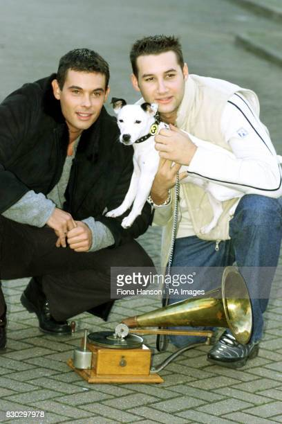Members of the boy band Another Level Dane Bowers and Mark Baron with Jack Russell terrier Meg after the dog was chosen as the new mascot for the HMV...