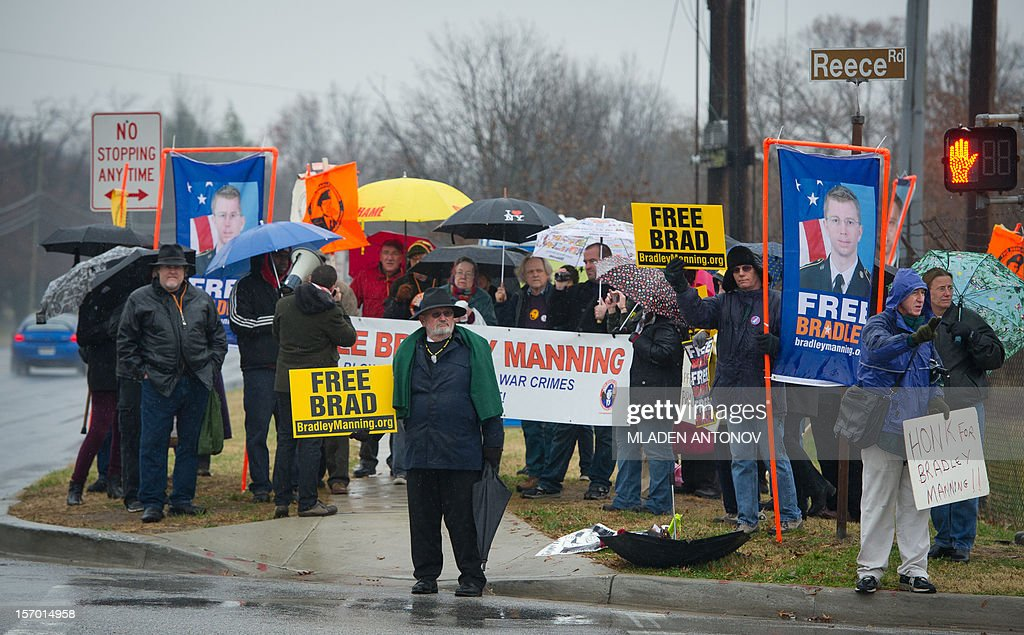 Members of the Bradley Manning Support Group protest under the rain during a rally at the entrance of Fort George G. Meade military base in Fort Meade, Maryland on November 27, 2012. Manning is accused of downloading 260,000 US diplomatic cables, videos of US air strikes and US military reports from Afghanistan and Iraq between November 2009 and May 2010 and turning them over to WikiLeaks in what has been called one of the most serious intelligence breaches in US history.