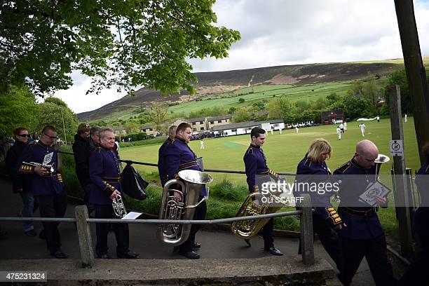Members of the Brighouse and Rastrick Band leave after competing in the Whit Friday brass band competition in the village of Greenfield near Oldham...