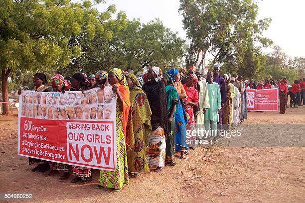 Members of the 'Bring Back Our Girls' movement and mothers of the missing schoolgirls holding a banner showing photographs of some of the missing...