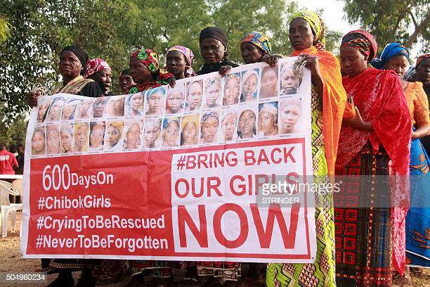 Members of the 'Bring Back Our Girls' movement holding a banner showing photographs of some of the missing march to press for the release of the...