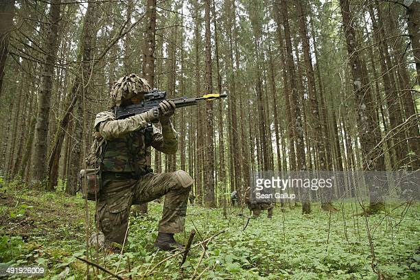 Members of the British Duke of Lancaster's Regiment advance towards the enemy in a forest while participating in the NATO 'Spring Storm' military...