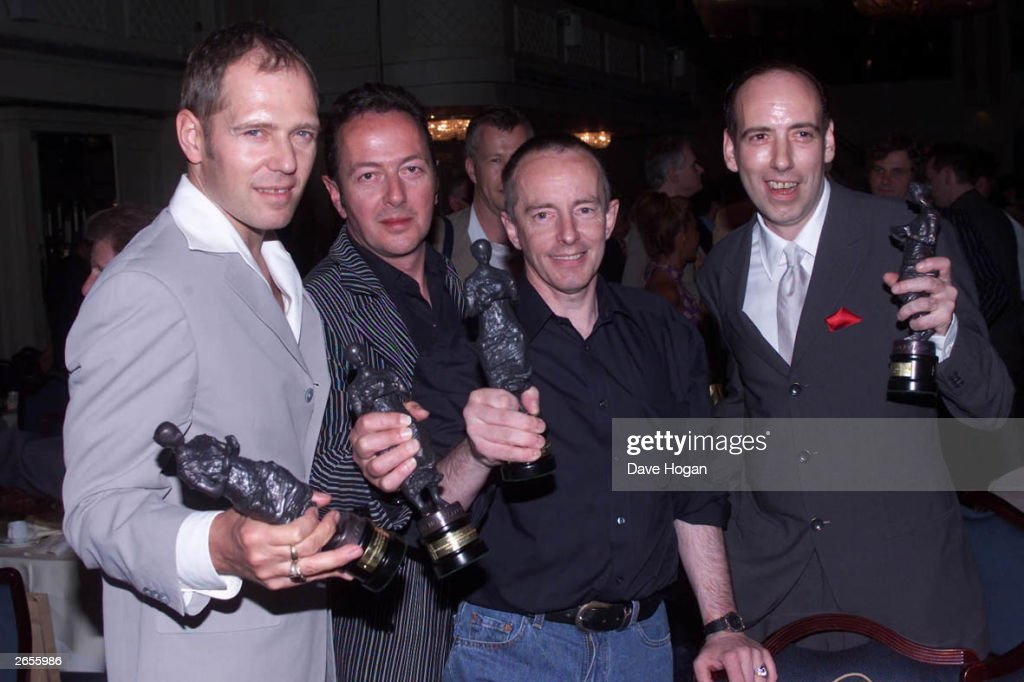 Members of the British punk band 'The Clash' after receiving an award for Outstanding Contribution to British Music at the Ivor Novello Awards at Grosvenor House Hotel Park Lane, London, May 24, 2001. Bandmembers present are (left to right) Paul Simonon, Joe Strummer (1952 - 2002), Nick Headon, and Mick Jones.