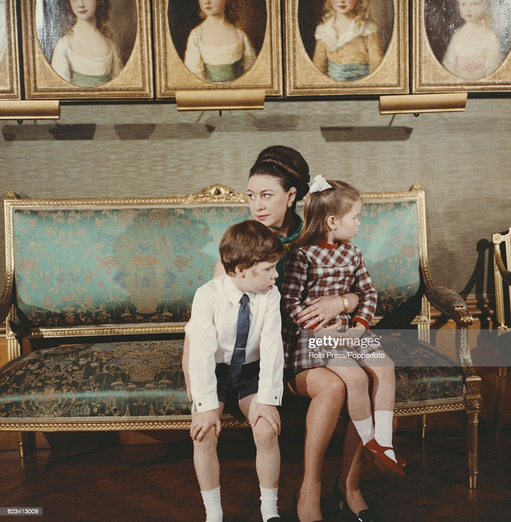 Members of the British Royal Family, Princess Margaret, Countess of Snowdon (1930-2002) pictured holding her children, David Armstrong-Jones, Viscount Linley and Lady Sarah Armstrong-Jones on her knees during filming of the television documentary 'Royal Family' in London in 1969. The documentary would be first broadcast to the nation's television viewers on 21st June 1969.