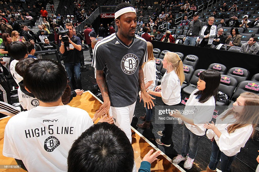 Members of the Brooklyn Nets shake hands with kids prior to the game against the Toronto Raptors at the Barclays Center on January 15, 2013 in the Brooklyn borough of New York City in New York City.