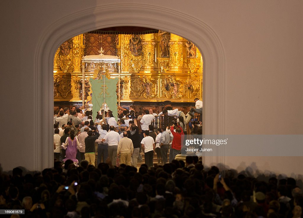 Members of the brotherhood of Matriz de Almonte jump the fence, el salto de la reja, after their simpecado has been brought in front of the chapel in the early hours of May 20, 2013 in Sanlucar De Barrameda, Spain. The Romeria del Rocio procession brings together roughly a million pilgrims each year making their way for as long as seven days from throughout Andalusia by foot, on horsebacks and horse drawn carriages, to the doors of the Hermitage of El Rocio. On Sunday night, after reciting the Holy Rosary at candlelight, and the passing of all the simpecados in front of the chapel, with the one from the brotherhood of Matriz de Almonte as the last one, el salto de la reja begins, the jumping of the fence surrounding the Hermitage after which the Virgin of El Rocio is carried out onto the sandy streets of the small town for the 'Blanca Paloma' procession. Then, the long camino home begins. Dating back from 1653, it was in 1758, when the Virgin of Las Rocinas became known as the Virgin of El Rocio, that the pilgrimage started to take place in the weekend of the Sunday of Pentecost, 50 days after Easter Sunday.