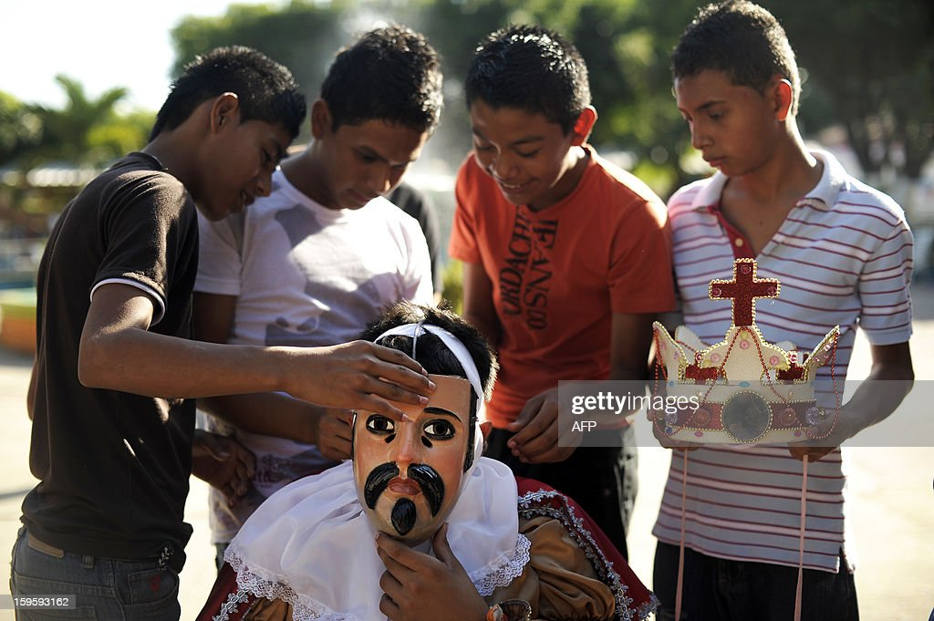 Members of the brotherhood of Saint Sebatian Matyr assist a dancer to get ready for the dance of The Moors and Christians in the town of Apastepeque, 50 kms east from San Salvador, El Salvador on January 16, 2013. The members of the Saint Sebastian brotherhood dance in the honor of the co-patron saint of Apatepeque. The Moors and Christians dance tells the adventures of the crusadaders and is celebrated from more than 300 years ago. AFP PHOTO/ Jose CABEZAS