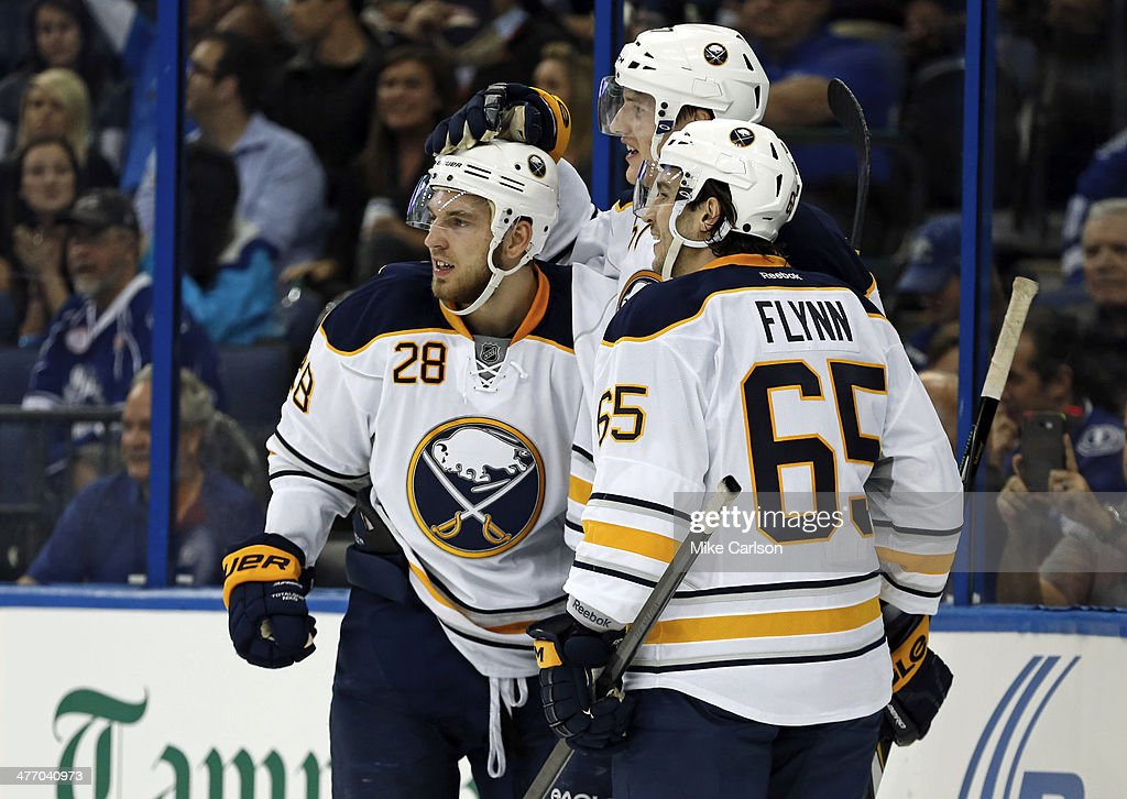 Members of the Buffalo Sabres (L-R) <a gi-track='captionPersonalityLinkClicked' href=/galleries/search?phrase=Zemgus+Girgensons&family=editorial&specificpeople=8050732 ng-click='$event.stopPropagation()'>Zemgus Girgensons</a> #28, <a gi-track='captionPersonalityLinkClicked' href=/galleries/search?phrase=Tyler+Myers&family=editorial&specificpeople=4595080 ng-click='$event.stopPropagation()'>Tyler Myers</a> #57, and Brian Flynn #65 celebrate a goal against the Tampa Bay Lightning at the Tampa Bay Times Forum on March 6, 2014 in Tampa, Florida.