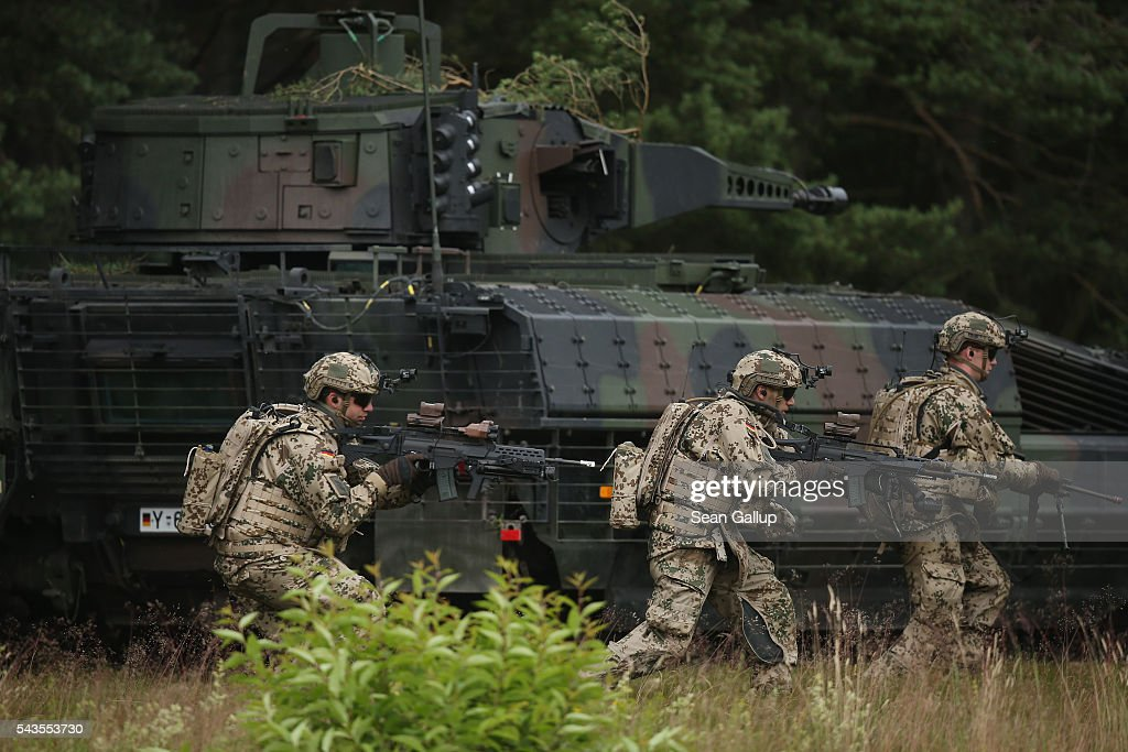 Members of the Bundeswehr, the German armed forces, run past a Puma infantry fighting vehicle during a demonstration of capablities of Panzergranadierbataillon 33 of the 1st Panzer Division (1. Panzerdivision) on June 29, 2016 near Neustadt am Ruebenberge, Germany. The Bundeswehr is aquirung the Puma in phases and the vehicle replaces the Marder.