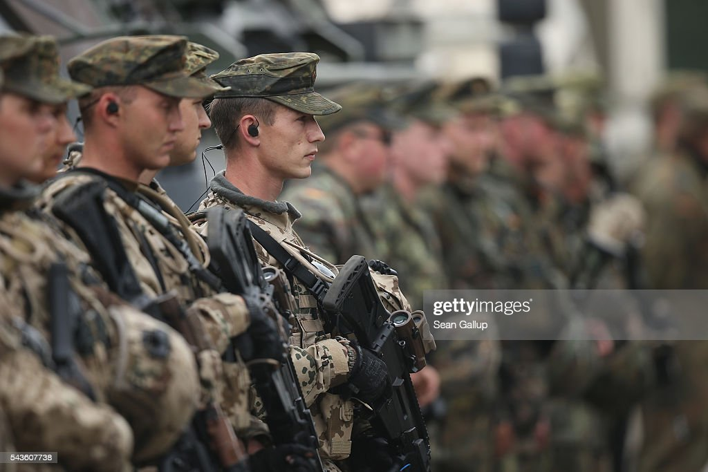 Members of the Bundeswehr, the German armed forces, stand at attention after they particpated in a demonstration of capabilities of Panzergranadierbataillon 33 of the 1st Panzer Division (1. Panzerdivision) that included the new Puma infantry fighting vehicle on June 29, 2016 near Neustadt am Ruebenberge, Germany. The Bundeswehr is aquirung the Puma in phases and the vehicle replaces the Marder.