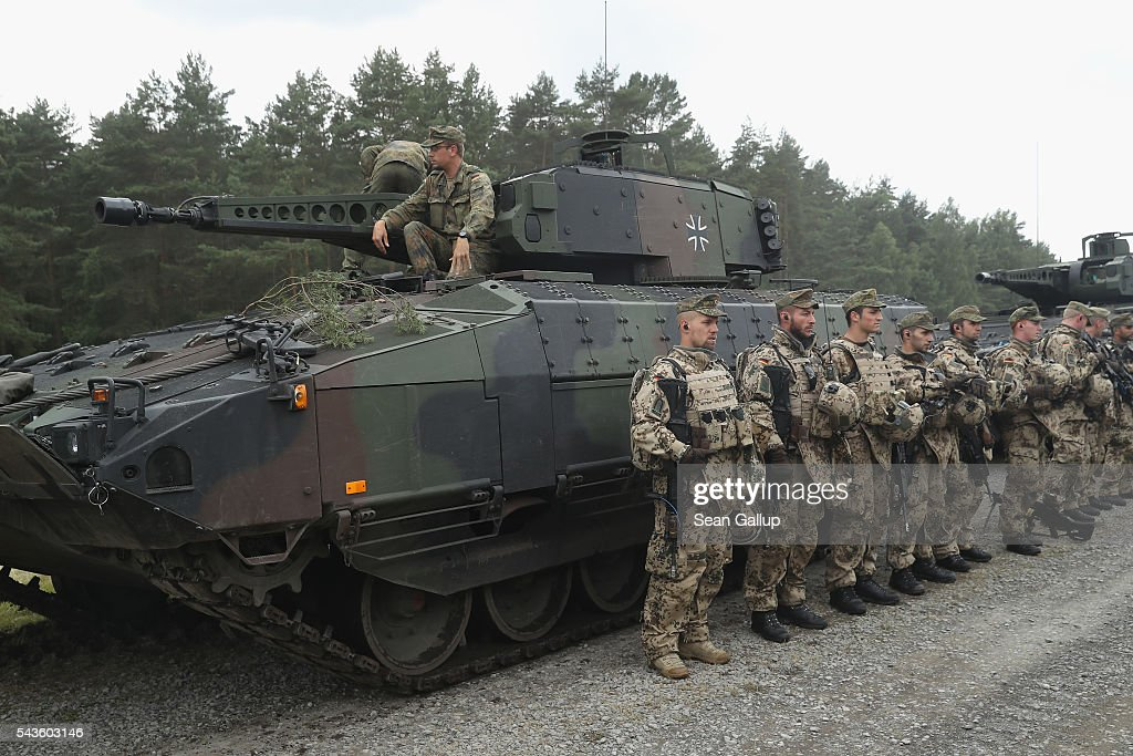 Members of the Bundeswehr, the German armed forces, stand next to Puma infantry fighting vehicles following a demonstration of capablities of Panzergranadierbataillon 33 of the 1st Panzer Division (1. Panzerdivision) on June 29, 2016 near Neustadt am Ruebenberge, Germany. The Bundeswehr is aquirung the Puma in phases and the vehicle replaces the Marder.