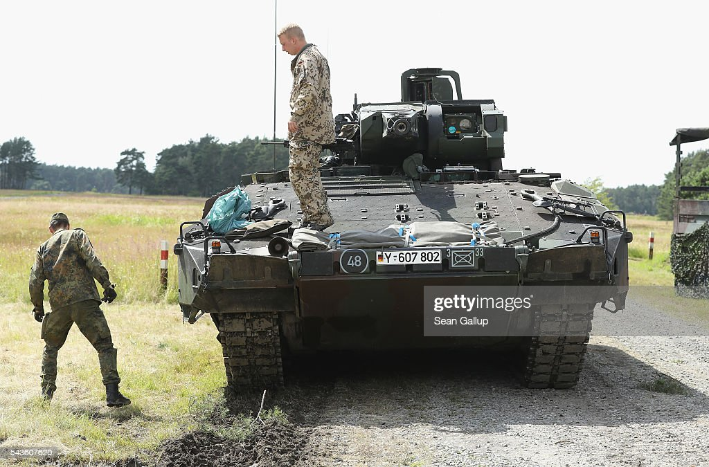 Members of the Bundeswehr, the German armed forces, step down from a Puma infantry fighting vehicle following a demonstration of capabilities of Panzergranadierbataillon 33 of the 1st Panzer Division (1. Panzerdivision) on June 29, 2016 near Neustadt am Ruebenberge, Germany. The Bundeswehr is aquirung the Puma in phases and the vehicle replaces the Marder.