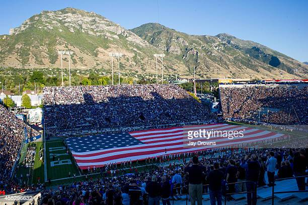 Members of the BYU ROTC program and players from the University of Houston Cougars and the Brigham Young University Cougars hold a flag over the...