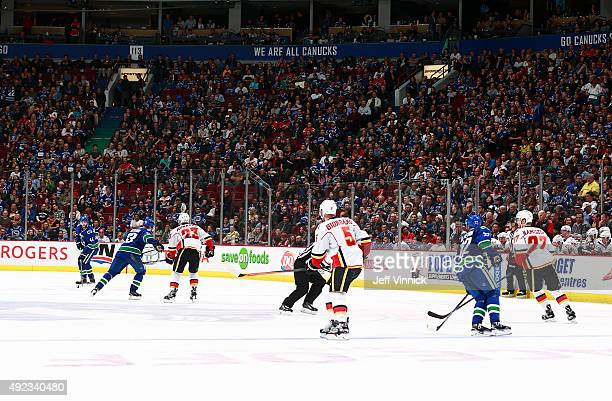 Members of the Calgary Flames and the Vancouver Canucks play threeonthree in overtime during their NHL game at Rogers Arena October 10 2015 in...