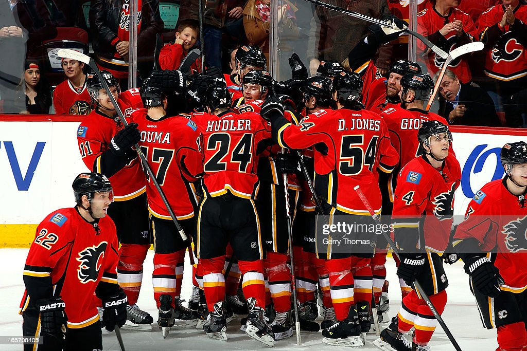 Members of the Calgary Flames celebrate a 5-4 overtime win against the Chicago Blackhawks at Scotiabank Saddledome on January 28, 2014 in Calgary, Alberta, Canada.