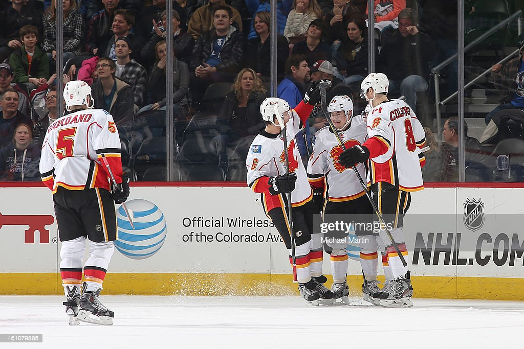 Members of the Calgary Flames skate to teammate <a gi-track='captionPersonalityLinkClicked' href=/galleries/search?phrase=Mike+Cammalleri&family=editorial&specificpeople=634009 ng-click='$event.stopPropagation()'>Mike Cammalleri</a> #13 to celebrate his go-ahead goal late in the third period against the Colorado Avalanche at the Pepsi Center on January 06, 2014 in Denver, Colorado. The Flames defeated the Avalanche 4-3. Ê