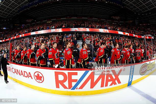 Members of the Calgary Flames stand for the national anthem before an NHL game against the Minnesota Wild on December 2 2016 at the Scotiabank...