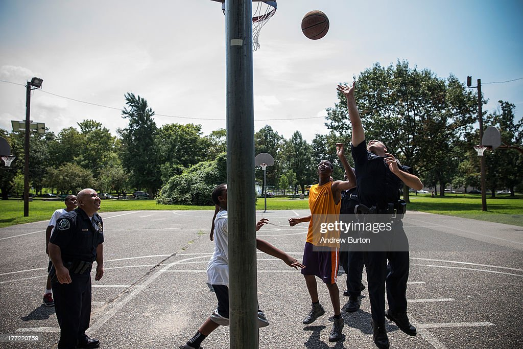Members of the Camden County Police Department (CCPD) play basketball with locals during a day of action organized by the CCPD, on August 22, 2013 in the Parkside neighborhood of Camden, New Jersey. The day of action included the cleaning of Farnham Park and general neighborhood interaction between the CCPD, faith leaders and locals. The town of Camden, which was once a large industrial town but watched it's population dwindle as manufacturing left, has been marred with societal problems including high unemployment, crime, murder and heavy drug trafficking for decades. The Camden County Police Department was officially created in May, 2013, after the unionized Camden Police department was disbanded. The overhaul, which was supported by New Jersey Governor Chris Christie, has been considered unprecendented and has been closely watched around the country. The new force currently has approximately 280 members, and will reach full size by December, with 400 members. Early signs suggest the overhaul has been effective - The Wall Street Journal reported earlier this month that Camden murder rates fell 29% from May, 2013 to July 2013, compared to the same period last year. Absentee rates of the CCPD is also lower: approximately 5% of officers have been reported absent so far, compared to approxmiately 30% of the Camden Police Department prior to the change in command.