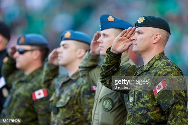 Members of the Canadian Forces salute during the national anthem before the game between the BC Lions and the Saskatchewan Roughriders at Mosaic...