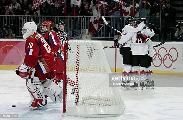 Members of the Canadian women's ice hockey team congratulate Danielle Goyette on her goal early in the first period as goalie Irina Gashennikova of...