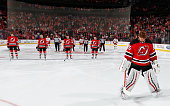 Members of the Carolina Hurricanes and the New Jersey Devils stand for a moment of silence in honor of the two New York City Police Officers slain in...