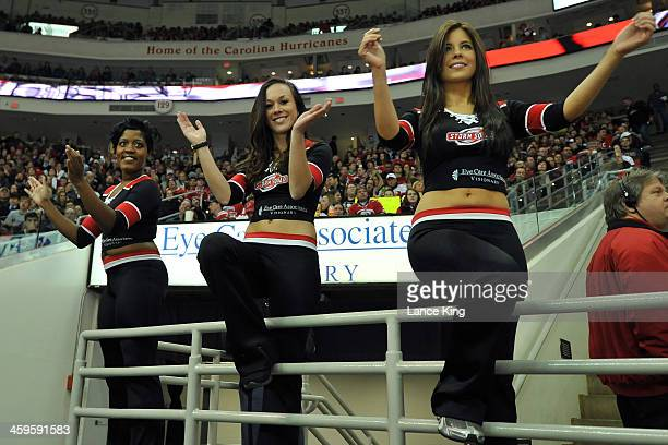 Members of the Carolina Hurricanes Storm Squad cheer against the Pittsburgh Penguins at PNC Arena on December 27 2013 in Raleigh North Carolina The...