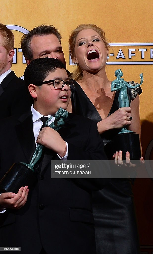 Members of the cast of Modern Family pose with the Screen Actors Guild Award for for Oustanding Performance by an Ensemble in a Comedy Series in the press room at the Shrine Auditorium in Los Angeles on January 27, 2013. AFP PHOTO / Frederic J. BROWN