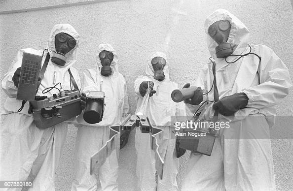 Members of the Cellule Mobile d'Intervention Radiologique unit of French firefighters in protective chemical suits hold equipment used to measure...