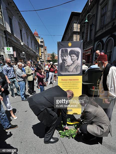 Members of the CentralEuropean Monarchists delegation set up a banner and lay flowers on June 28 2014 during commemorations marking the 100th...