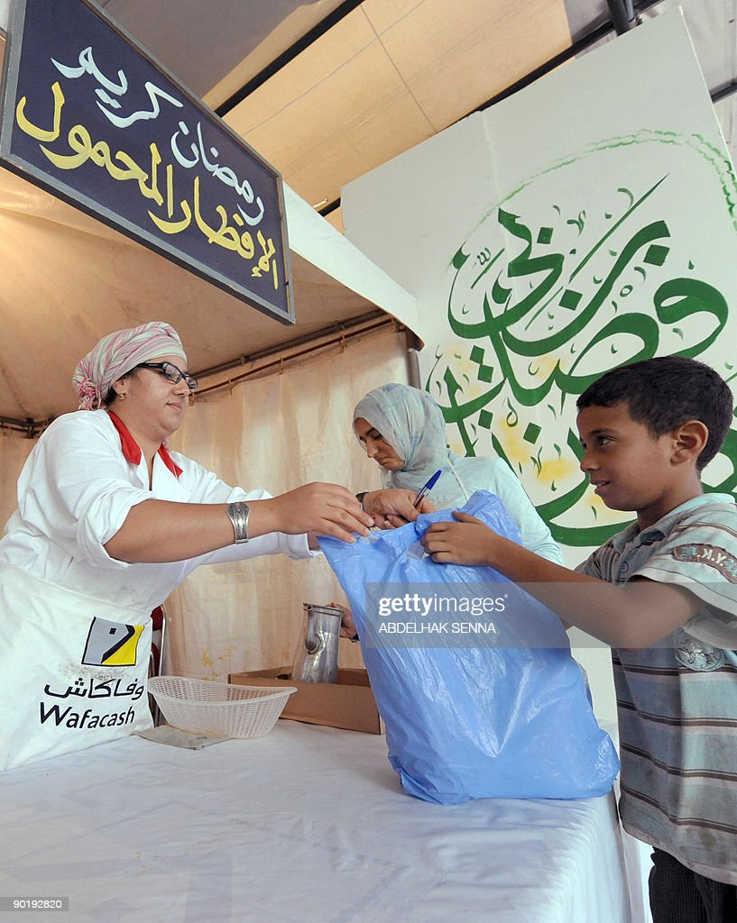 Members of the charitable association 'Al Wifak' give out provisions in Casablanca on August 29, 2009 to poor families during the Muslim holy month of Ramadan.