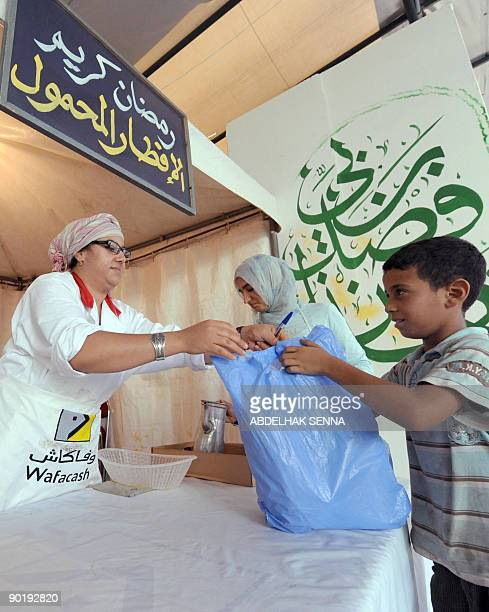 Members of the charitable association 'Al Wifak' give out provisions in Casablanca on August 29 2009 to poor families during the Muslim holy month of...