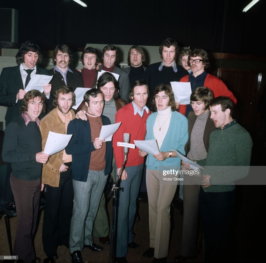 Members of the Chelsea football squad recording their song 'Blue Is The Colour', a month before their (ultimately unsuccessful) appearance in the Football League Cup Final against Stoke City, 3rd February 1972. Back row, left to right: Paddy Mulligan, Charlie Cooke, John Hollins, Marvin Hinton, David Webb, Peter Osgood, Chris Garland and Eddie McCreadie. Front row: Steve Kember, Tommy Baldwin, Ron Harris, Micky Droy, John Dempsey, Alan Hudson, John Phillips and Peter Houseman.