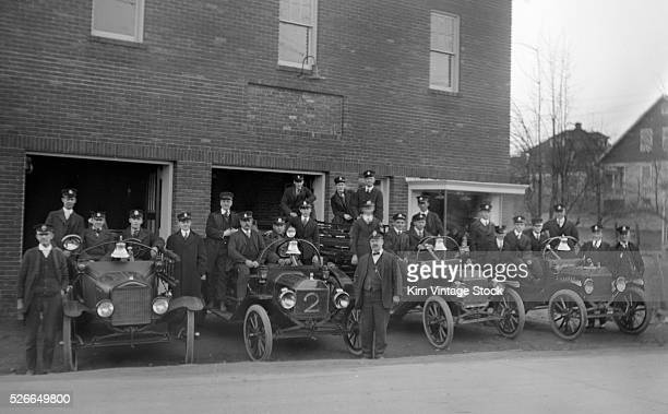 Members of the Cherrydale Volunteer Fire Department in Arlington Virginia pose with their trucks in the newly built firehouse in 1919