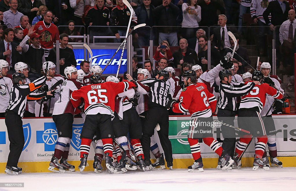 Members of the Chicago Blackhawks and the Colorado Avalanche get into a shoving match along the boards at the United Center on March 6, 2013 in Chicago, Illinois.