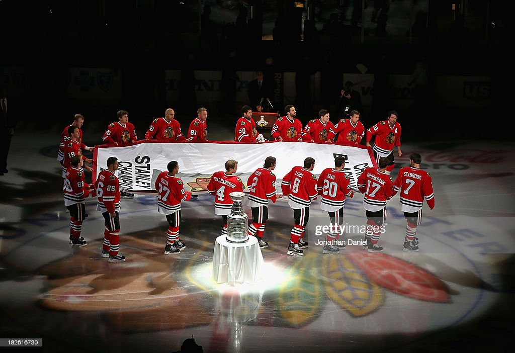 Members of the Chicago Blackhawks carry the Championship banner past the Stanley Cup during a ceremony before taking on the Washington Capitals at the United Center on October 1, 2013 in Chicago, Illinois.