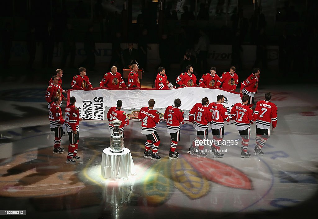 Members of the Chicago Blackhawks carry the Championship banner past the Stanley Cup during a ceremony before taking on the Washington Capitals at the United Center on October 1, 2013 in Chicago, Illinois. The Blackhawks defeated the Capitals 6-4.