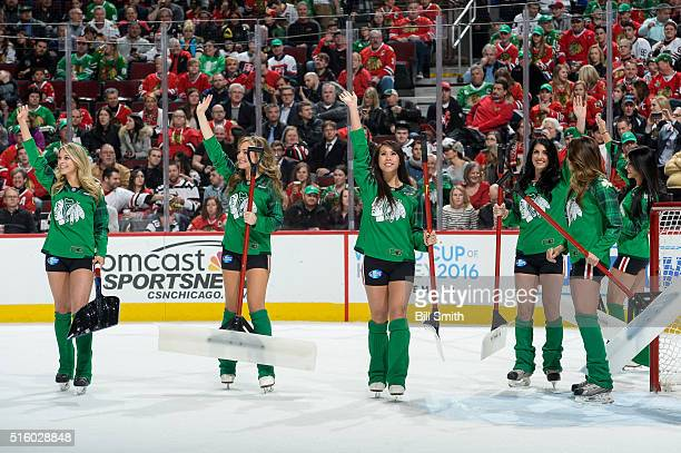 Members of the Chicago Blackhawks icecrew wave to the crowd while dressed for St Patrick's Day in the first period of the NHL game at the United...