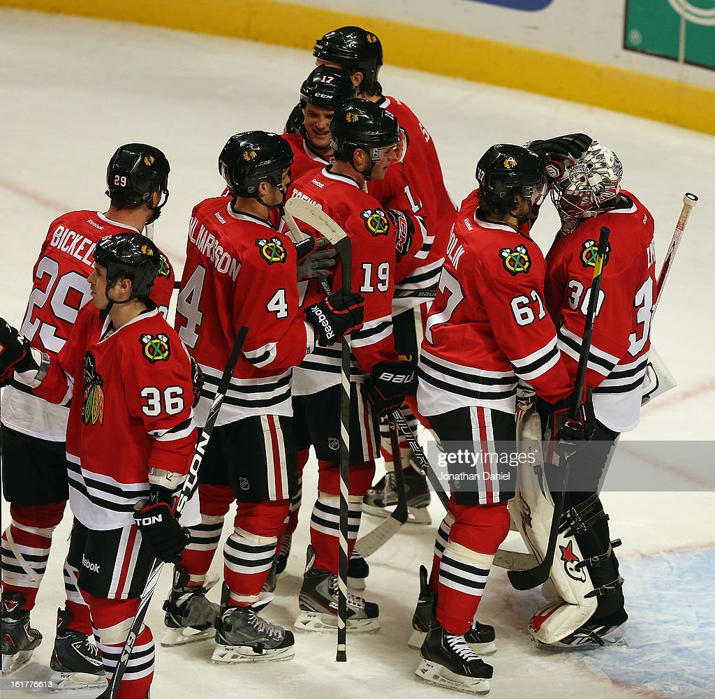 Members of the Chicago Blackhawks including Niklas Hjalmasson #4, <a gi-track='captionPersonalityLinkClicked' href=/galleries/search?phrase=Jonathan+Toews&family=editorial&specificpeople=537799 ng-click='$event.stopPropagation()'>Jonathan Toews</a> #19 and <a gi-track='captionPersonalityLinkClicked' href=/galleries/search?phrase=Michael+Frolik&family=editorial&specificpeople=537965 ng-click='$event.stopPropagation()'>Michael Frolik</a> #67 congratulate <a gi-track='captionPersonalityLinkClicked' href=/galleries/search?phrase=Ray+Emery&family=editorial&specificpeople=218109 ng-click='$event.stopPropagation()'>Ray Emery</a> #30 after a win over the San Jose Sharks at the United Center on February 15, 2013 in Chicago, Illinois. The Blackhawks defeated the Sharks 4-1.