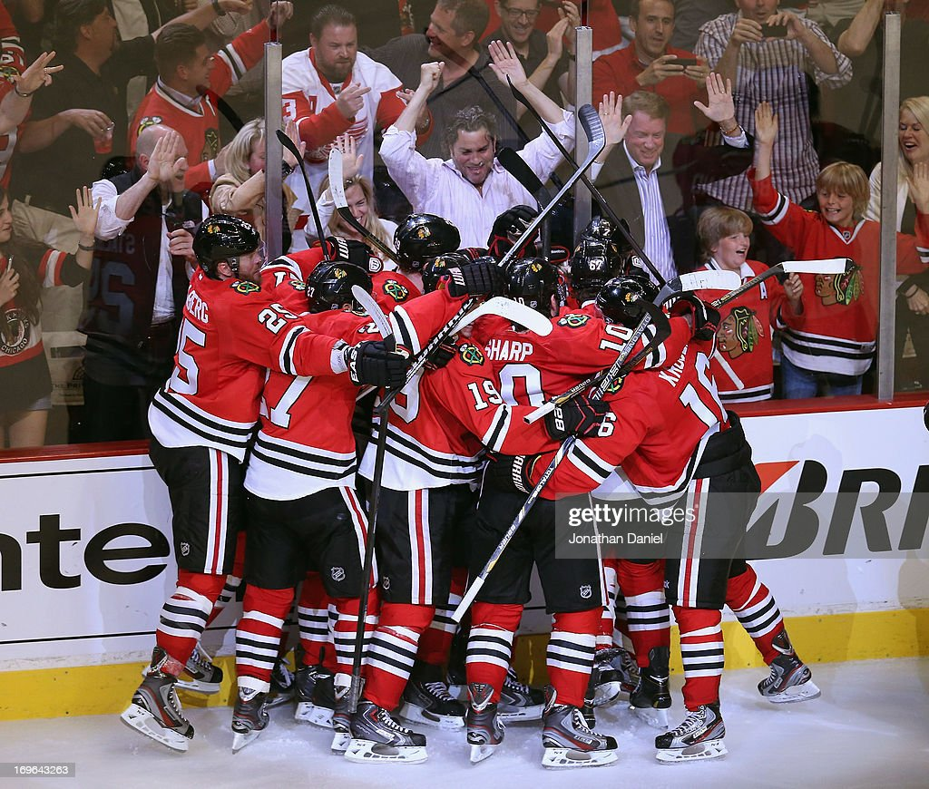 Members of the Chicago Blackhawks mob teammate Brent Seabrook after Seabrook scored the game-winning goal against the Detroit Red Wings in Game Seven of the Western Conference Semifinals during the 2013 NHL Stanley Cup Playoffs at the United Center on May 29, 2013 in Chicago, Illinois. The Blackhawks defeated the Red Wings 2-1 in overtime.