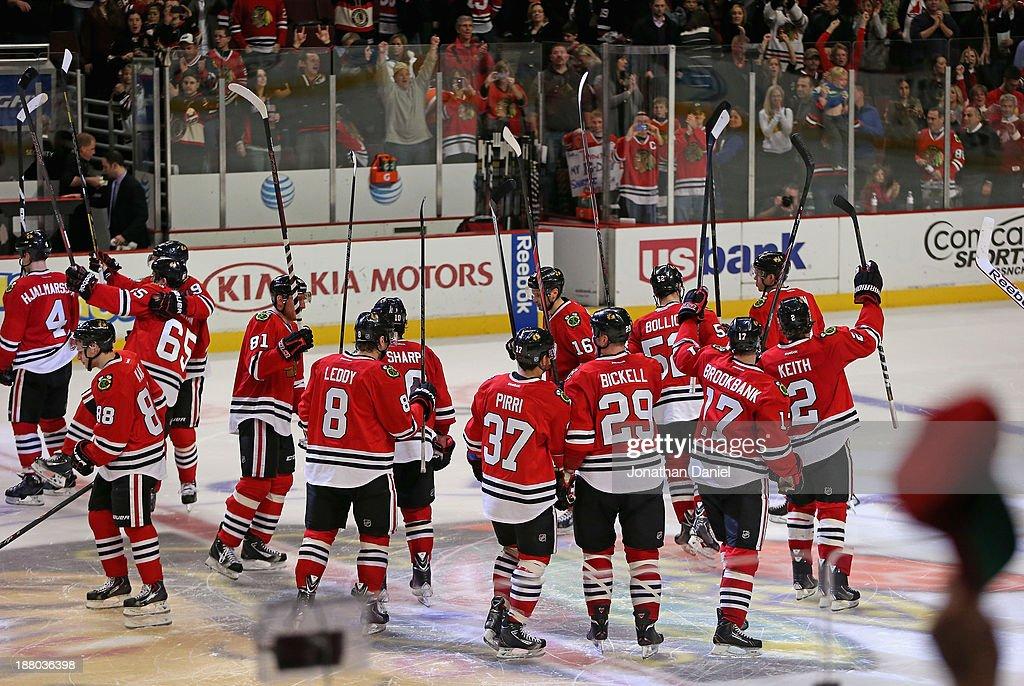 Members of the Chicago Blackhawks salute the crowd after a win over the Phoenix Coyotes at the United Center on November 14, 2013 in Chicago, Illinois. The Blackhawks defeated the Coyotes 5-4 in a shootout.