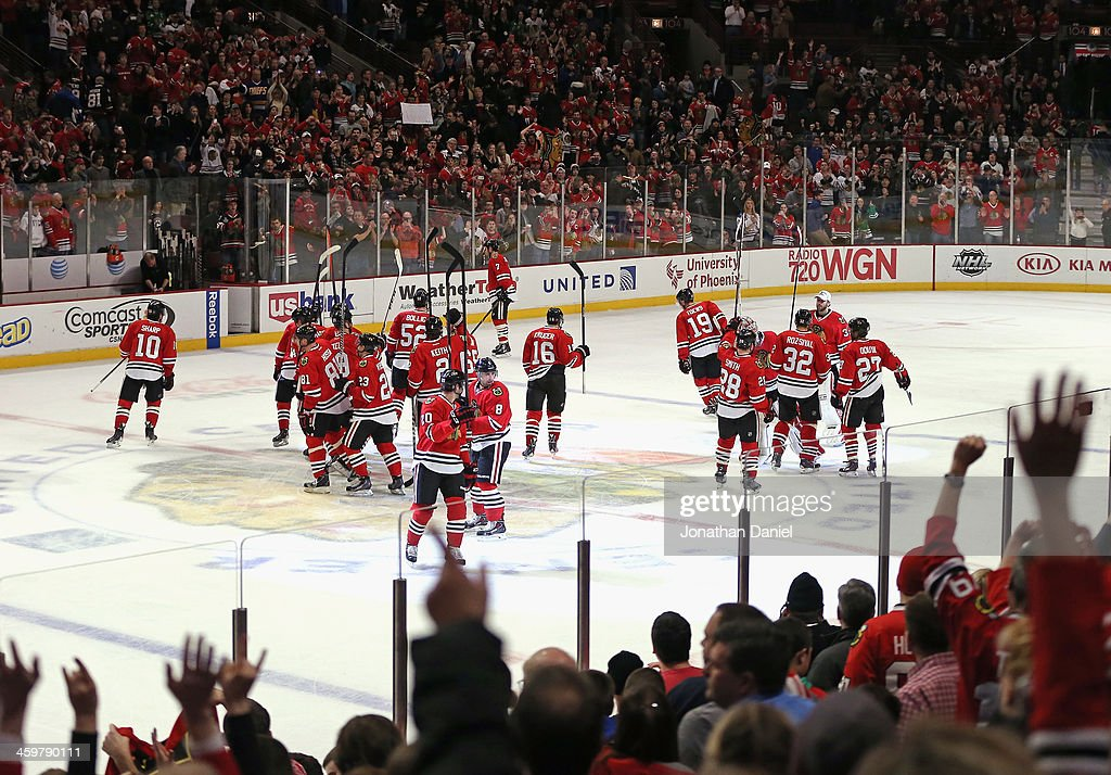 Members of the Chicago Blackhawks salute the crowd after a win over the Los Angeles Kings at the United Center on December 30, 2013 in Chicago, Illinois. The Blackhawks defeated the Kings 1-0.